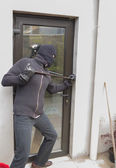 Burglar breaking door — Stock Photo