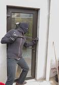 Burglar breaking door — Stock Photo