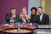 Four toasting with champagne at roulette — Stock Photo