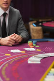 Man sitting at poker table with cards and chips — Stock Photo