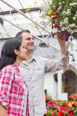 Couple admiring hanging flower basket — Stock Photo