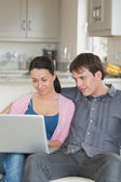 Young couple relaxing on the couch while using the laptop — Stock Photo