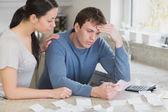 Worried couple looking over bills — Stock Photo