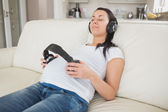 Pregnant woman holding headphones to belly and listening to music — Stock Photo
