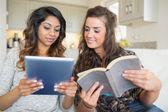 Dwie dziewczyny, czytając książkę i posiadania komputera typu tablet — Zdjęcie stockowe