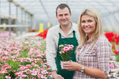 Smiling woman holding flower pot with employee — Stock Photo