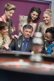Man surrounded by women accepting of loss — Stock Photo