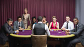 Smiling group sitting around poker table — Stock Photo
