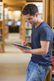Man leaning against book shelf using tablet pc — Stockfoto