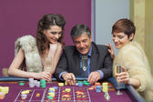 Man and two women talking at roulette table — Stock Photo