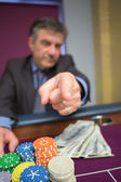Man with chips and cash pointing — Stock Photo