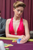 Woman sitting at table holding cards — Stock Photo
