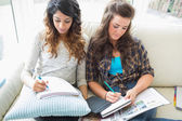 Two women sitting in a couch writing notepads — Stock Photo