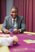 Smiling man looking up from poker — Stock Photo