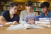 Mannen zitten in de bibliotheek kijken naar tablet pc — Stockfoto