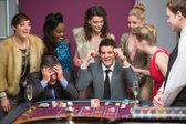 Człowiek zdobywając jako kolejny traci na stole do ruletki — Zdjęcie stockowe