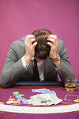 Depressed man playing poker — Stock Photo