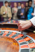 Dealer dropping ball into roulette wheel — Stock Photo