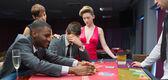 Women comforting man as other man takes jackpot — Stock Photo