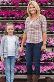 Mother and daughter holding hands in garden center — Stock Photo