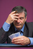 Man holding his cards thinking — Stock Photo