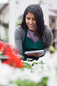Worker looking at the flowers and making notes — Stock Photo