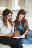 Two women sitting on a couch while looking at a notepad — Stock Photo