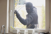 Burglar breaking a kitchen window — Stock Photo