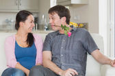 Man presenting a flower to the woman in his teeth — Stock Photo