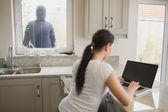 Woman being observed by burglar through window — Stock Photo