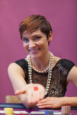 Woman in a casino holding dices — Stock Photo