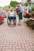 Woman in wheelchair buying potted plant — Stock Photo