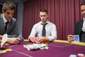 Men looking at their hands in high stakes poker game — Stock Photo