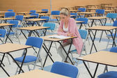 Student studying at desk in empty exam hall — Stock Photo