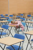 Student napping in exam hall — Stock Photo