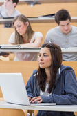 Girl sitting at the lecture hall concentrating — Stock Photo