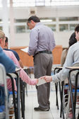 Students passing notes as teacher is talking to student — Stock Photo