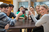 Students sitting clinking cups — Stock Photo