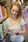 Woman standing at a bookshelf with tablet pc — Foto de Stock