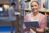 Woman leaning at a bookshelf holding a tablet pc — Stock Photo