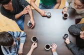Siedząc przy stole picia kawy — Zdjęcie stockowe