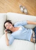 Uśmiechający się wzywając i leżąc na kanapie — Zdjęcie stockowe