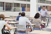 Dozent am anfang der klasse sprechen — Stockfoto