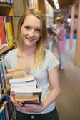 Student standing at a bookshelf at the library holding books — Stock Photo