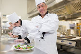 Chef smiling with others preparing salads — Stock Photo