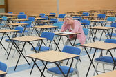 Student sitting at desk in empty exam hall — Stock Photo