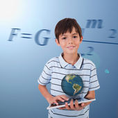 Little boy holding a tablet with a holographic globe hovering ov — Stock Photo