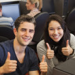 Happy students giving thumbs up — Stock Photo