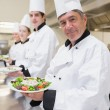 Cheerful Chef's showing their salads — Stock Photo