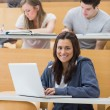 Smiling student in lecture with laptop — Stock Photo